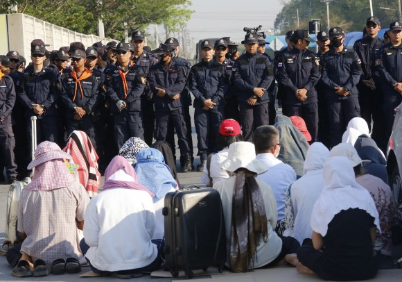 Buddhist pray in front of policemen outside the Wat Dhammakaya temple in Pathum Thani province, Thailand, on Feb. 16, 2017. (AP Photo/Sakchai Lalit)