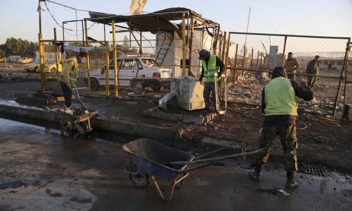 Baghdad municipality workers clean up the aftermath of a suicide car bomb attack at a used cars dealers parking lot in the eastern Habibiya neighborhood of Baghdad, Iraq on Feb. 16, 2017. (AP Photo/ Karim Kadim)