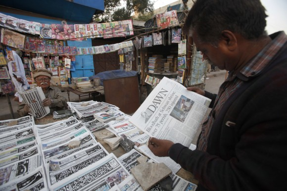A man reads a newspaper carrying headlines about Thursday's suicide bombing at the Lal Shahbaz Qalandar shrine, in Karachi, Pakistan, on Feb. 17, 2017. (AP Photo/Fareed Khan)