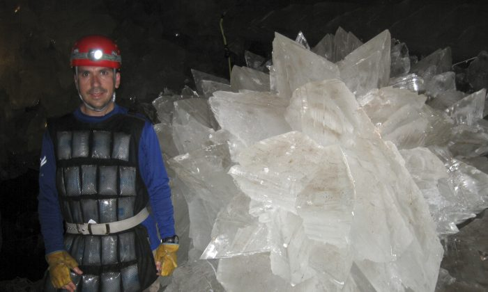 In this image provided by Mike Spilde, Mario Corsalini stands near to a gypsum rosette crystal. In a Mexican cave system so beautiful and hot that it is called both Fairyland and hell, scientists have discovered life trapped in crystals that could be 50,000 years old. (Mike Spilde via AP)