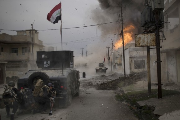 A car bomb explodes next to Iraqi special forces armored vehicles as they advance towards Islamic State held territory in Mosul, Iraq on Nov. 16, 2016. Troops have established a foothold in the city's east from where they are driving northward into the Tahrir neighborhood. The families in Tahrir are leaving their homes to flee the fighting. (AP Photo/Felipe Dana, File)