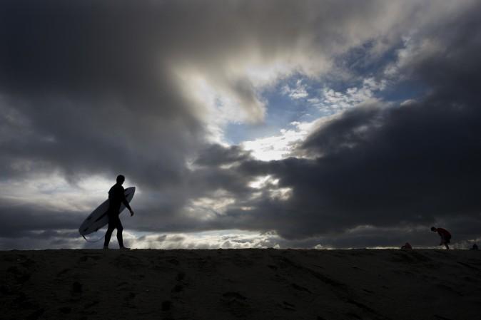 Surfer Bradley Domke walks along a sand berm as storm clouds gather overhead in Seal Beach, Calif., Feb. 18. (AP Photo/Jae C. Hong)