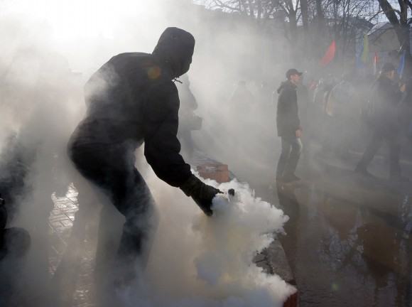 An activist throws a smoke grenade toward riot police during a protest rally in front of the President Office in Kiev, Ukraine on Feb. 19, 2017. Protesters were demanding a stop to trade relations with Russia-occupied Ukrainian territories. (AP Photo/Efrem Lukatsky)