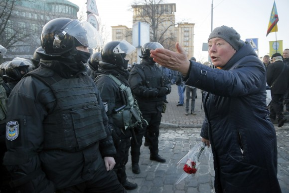 A woman holding a red carnation argues with riot police during a protest rally in front of the President Office in Kiev, Ukraine on Feb. 19, 2017. Protesters were demanding a stop to trade relations with Russia-occupied Ukrainian territories. (AP Photo/Efrem Lukatsky)