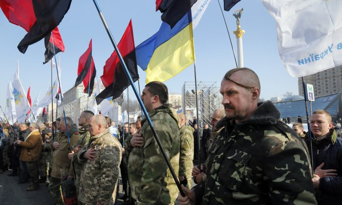 Ukrainian army veterans sing the national anthem to pay tribute to the victims of the 2013-2014 anti-government protests called the Revolution of Dignity, during commemoration events in central Kiev, Ukraine on Feb. 20, 2017. (AP Photo/Efrem Lukatsky)