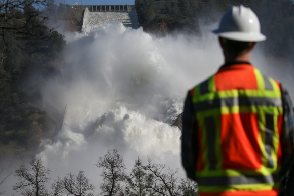 A worker keeps an eye on water coming down the damaged main spillway of the Oroville Dam in Oroville, Calif. on Feb. 14. (Photo by Elijah Nouvelage/Getty Images)