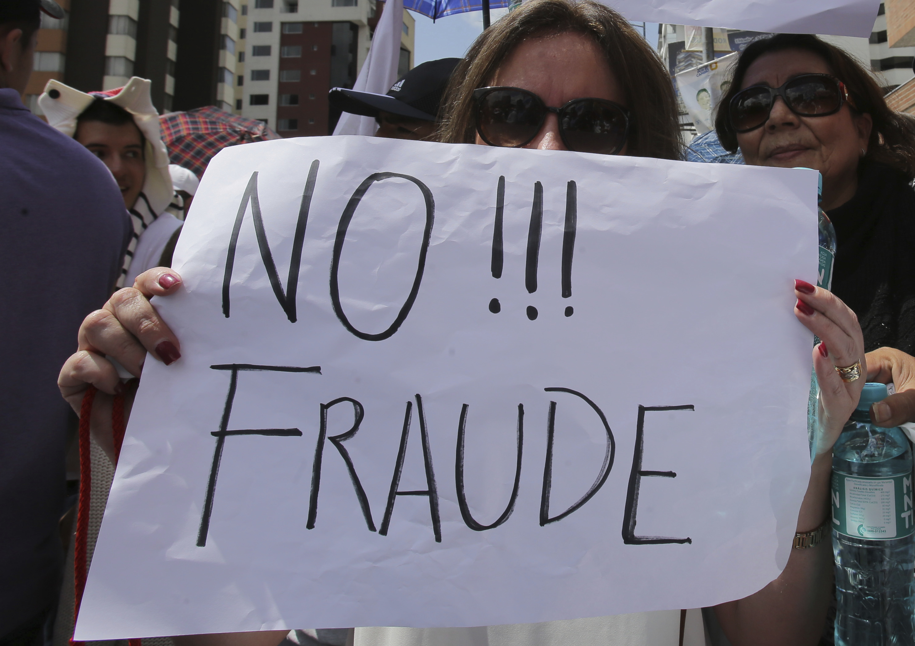 "An opposition presidential candidate Guillermo Lasso's supporter holds a sign that read in Spanish ""No to Fraud!"" during protest outside Ecuador's National Electoral Council to demand the official results of the presidential elections, in Quito, Ecuador on Feb. 20, 2017. (AP Photo/Dolores Ochoa)"