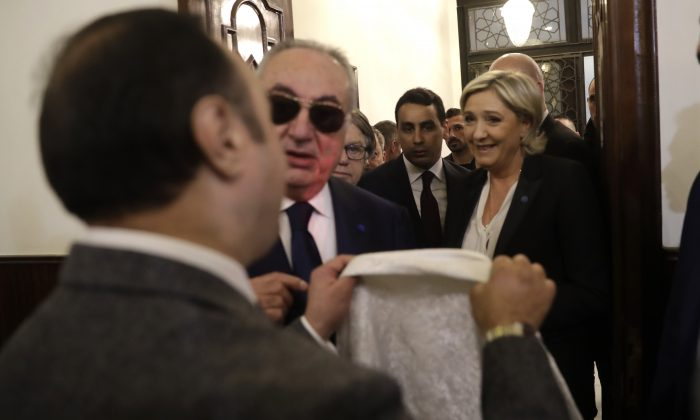 An aide of Lebanon's Grand Mufti Sheikh Abdel-Latif Derian (L) gives a head scarf to French conservative presidential candidate Marine Le Pen (R) to wear during her meeting with the Mufti, which Le Pen refused, upon her arrival at Dar al-Fatwa the headquarters of the Sunni Mufti, in Beirut, Lebanon on Feb. 21, 2017. (AP Photo/Hussein Malla)