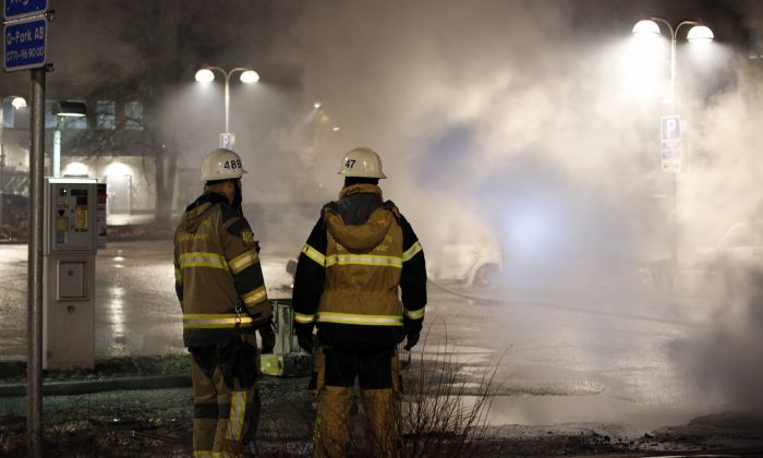 Firefighters survey the scene in the suburb of Rinkeby outside Stockholm on Feb. 20, 2017. Police in Sweden said Tuesday they were investigating riots that broke out overnight in a predominantly immigrant Stockholm suburb after officers arrested a suspect on drug charges. (Christine Olsson/TT News Agency via AP)