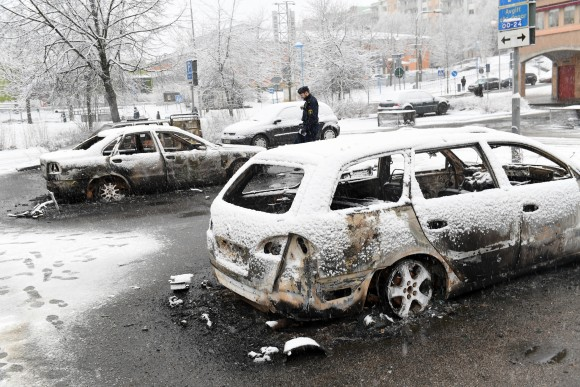 A policeman investigates a burned out car in the suburb of Rinkeby outside Stockholm on Feb. 20, 2017. Police in Sweden said Tuesday they were investigating riots that broke out overnight in a predominantly immigrant Stockholm suburb after officers arrested a suspect on drug charges. Spokesman Lars Bystrom said unidentified people, including some wearing masks, threw rocks at police, set cars on fire and looted shops in Rinkeby, north of Stockholm. (Christine Olsson/TT News Agency via AP)