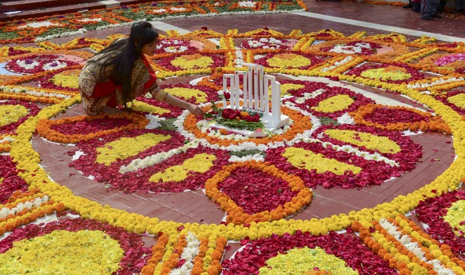 A Bangladeshi woman decorates the Bangladesh Central Language Martyrs' Memorial monument with flowers in homage to the martyrs of the 1952 Bengali Language Movement in Dhaka on Feb. 21, 2017. International Mother Language Day is celebrated each year on this day, marking 65 years since police officials fired at thousands of protesters at universities in then East Pakistan, who were demanding that Bengali be declared the state language. The deaths marked the start of a nearly two-decades-long struggle for the establishment of the state Bangladesh which was achieved when Indian troops were victorious in the 1971 independence war with Pakistan. (STR/AFP/Getty Images)