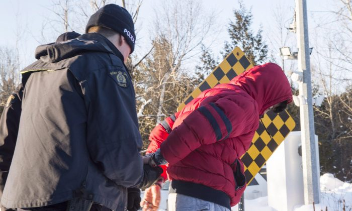 A young man from Yemen is handcuffed by an RCMP officer after crossing the border into Canada near Hemmingford, Que., on Feb. 17, 2017. (The Canadian Press/Paul Chiasson)