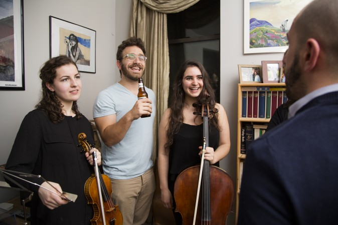 Sam Bodkin, CEO of Groupmuse, at a house concert with Rannveig Marta Sarc (L) and Clara Abel in Harlem, New York, on Feb. 17, 2017. (Samira Bouaou/Epoch Times)