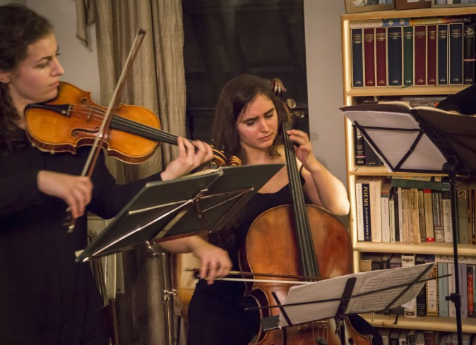 Clara Abel on cello perform (R) and Rannveig Marta Sarc on violin at a Groupmuse house concert in Harlem, New York, on Feb. 17, 2017. (Samira Bouaou/Epoch Times)