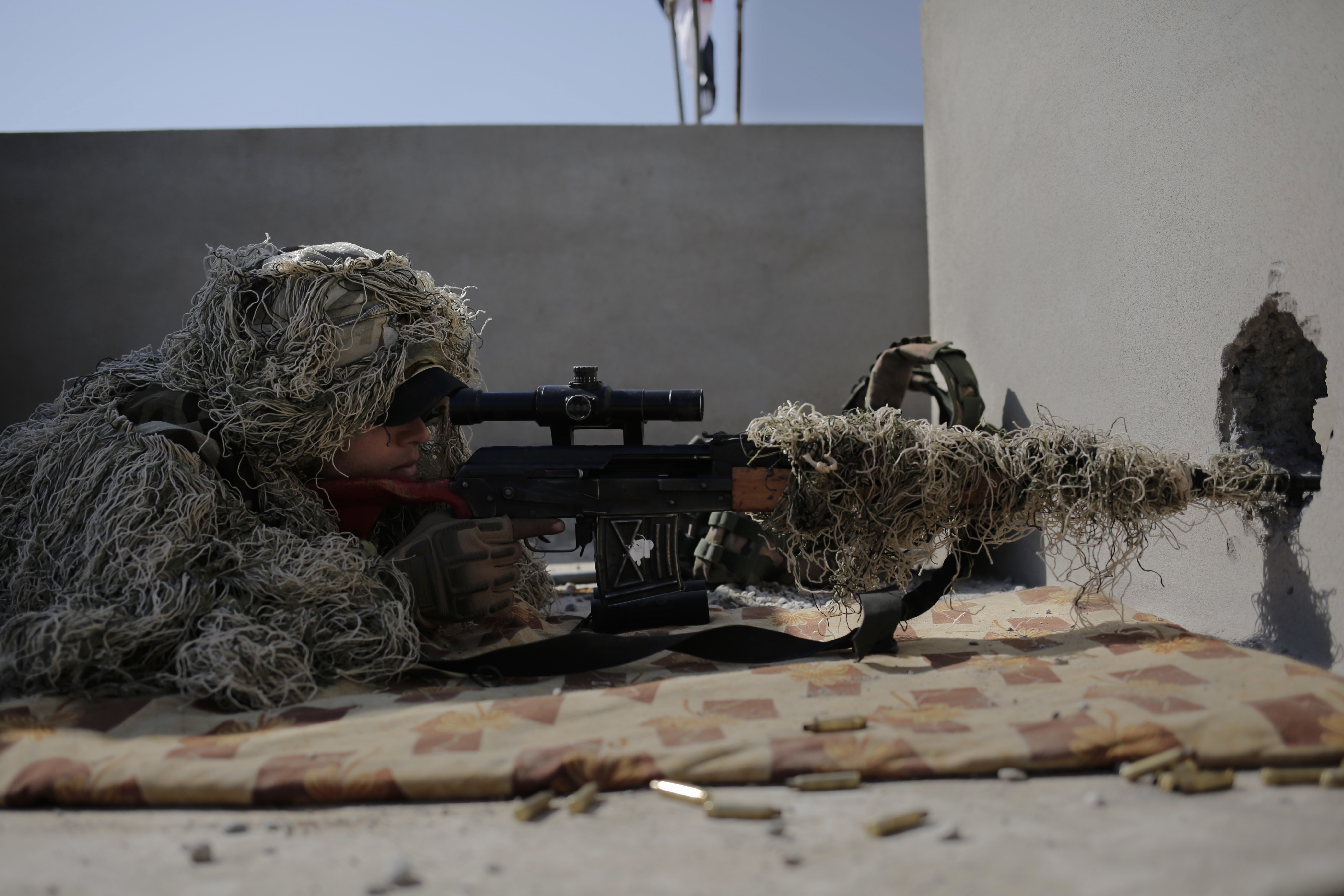 A sniper with the Iraqi federal police aims at an ISIS position from the rooftop of a house in the town of Abu Saif, on Feb. 22, 2017. (AP Photo/Bram Janssen)