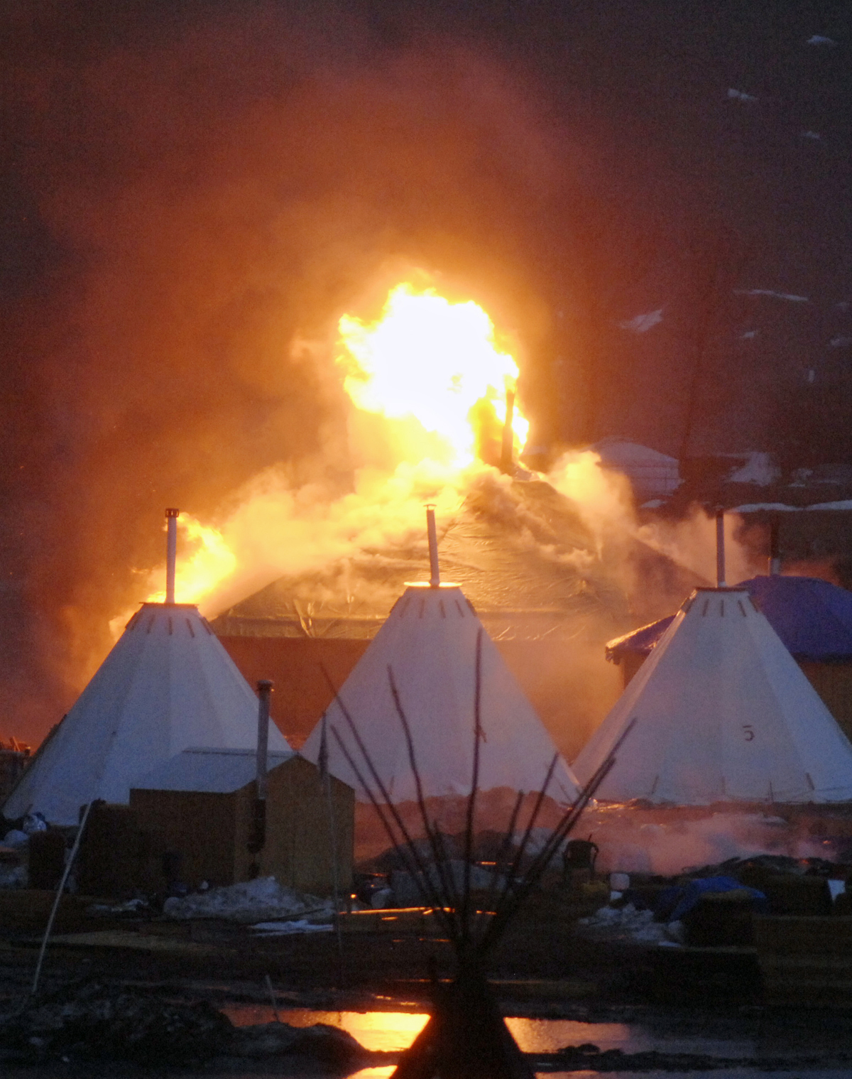 A fire on a building at a camp that has been home to demonstrators against the Dakota Access pipeline is seen after protesters set fire in Cannon Ball, N.D., on Feb. 22, 2017. (Mike Mccleary/The Bismarck Tribune via AP)