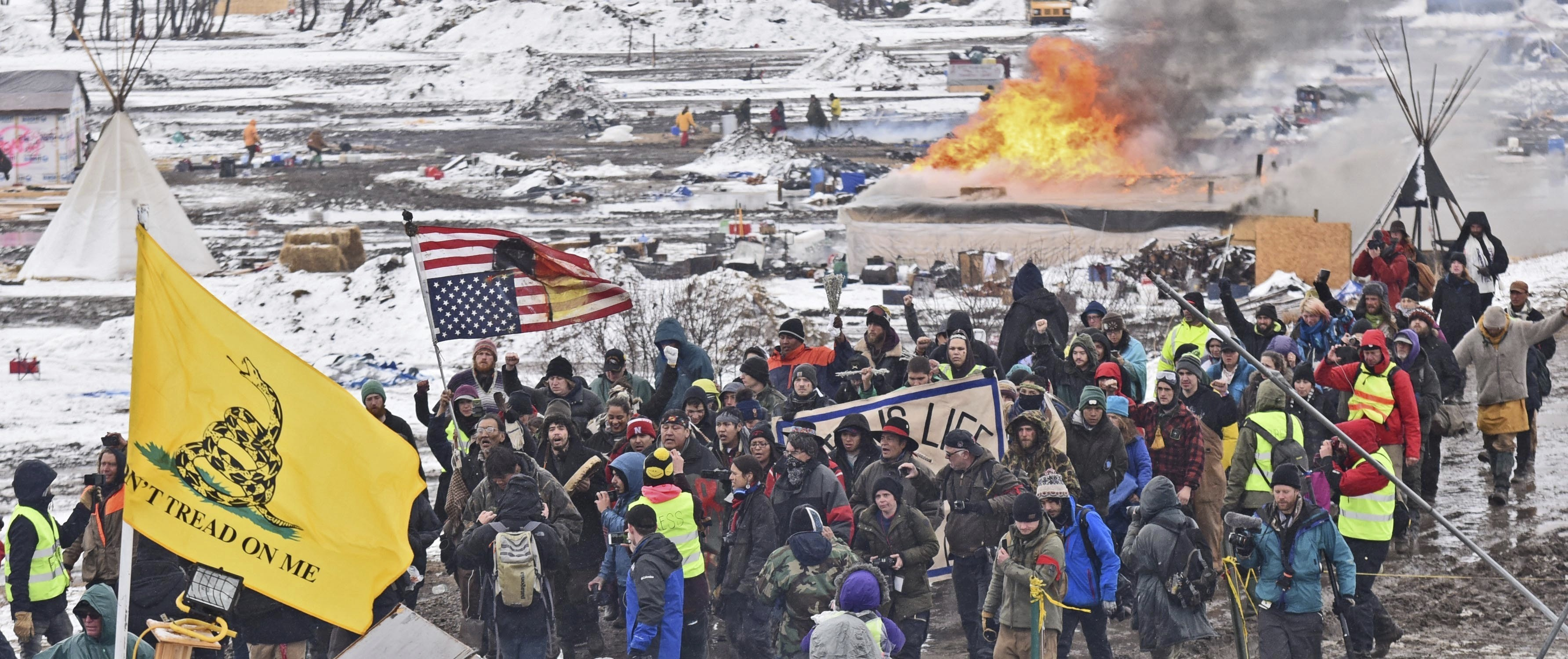 A fire set by protesters burns in the background as opponents of the Dakota Access pipeline leave their main protest camp near Cannon Ball, N.D., on Feb. 22, 2017. (Tom Stromme/The Bismarck Tribune via AP)