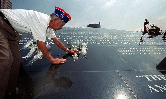 "Japanese-American World War II soldier George Yamada places flowers on the ""Go for Broke Monument"", in downtown Los Angeles, on June 5, 1999. (LUCY NICHOLSON/AFP/Getty Images)"