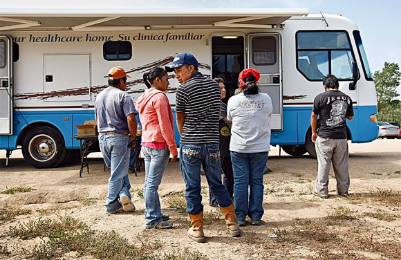 Migrant workers from Mexico line up for flu shots at a farm in Colorado. Although most illegal migrants are limited to low-skill jobs, many feel they are better off than in their home countries, where gangs and violence may dominate work and public life. (John Moore/Getty Images)