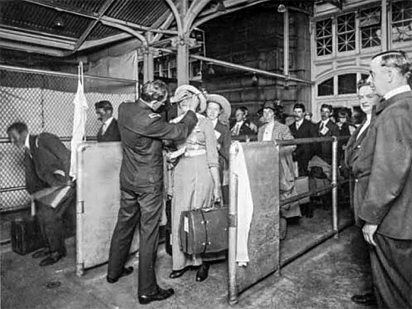 An immigration inspector performs eye examinations on immigrants arriving at Ellis Island in New York in the early 1900s. (National Archives)