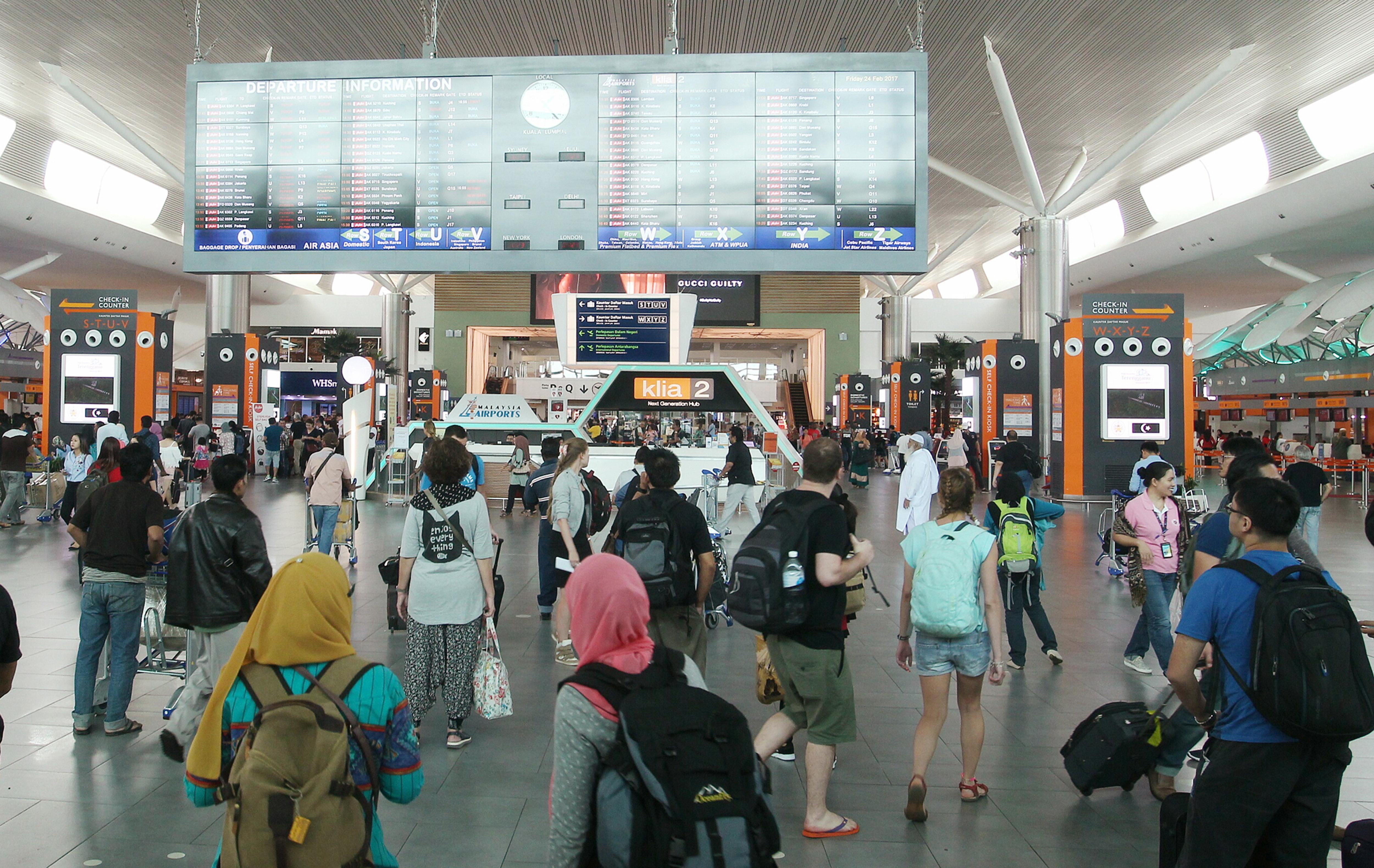 Passengers scan departure information at the Kuala Lumpur International Airport in Sepang, Malaysia on Feb. 24, 2017. (AP Photo)