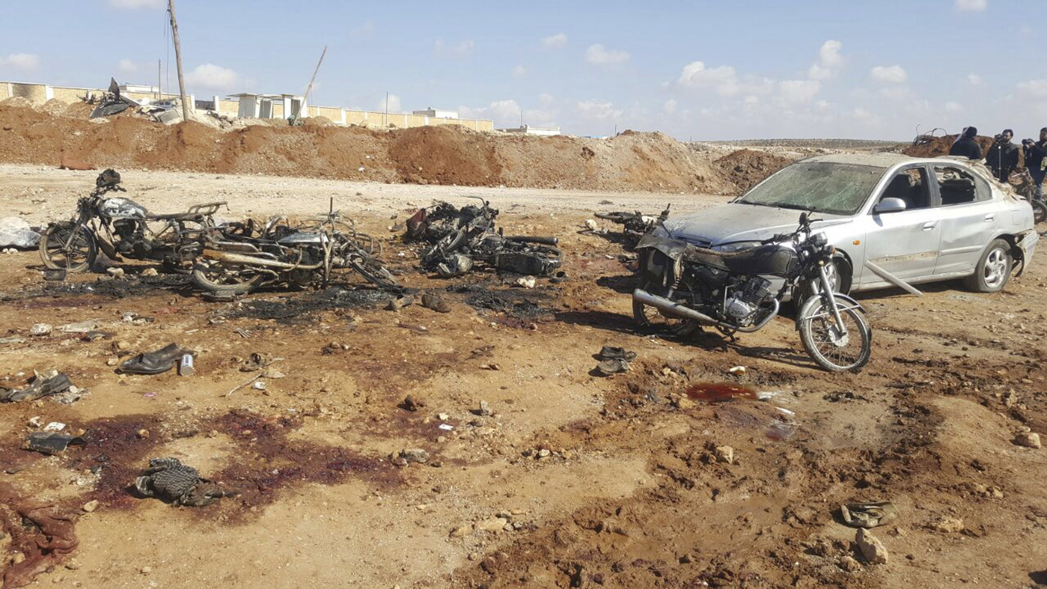 Burned motorcycles and car damaged after a suicide attacker blew his small pick-up truck outside a security office in Sousian village, about 8 kilometers (5 miles) north of al-Bab, Syria on Feb. 24, 2017. (Thiqa News Agency, via AP)