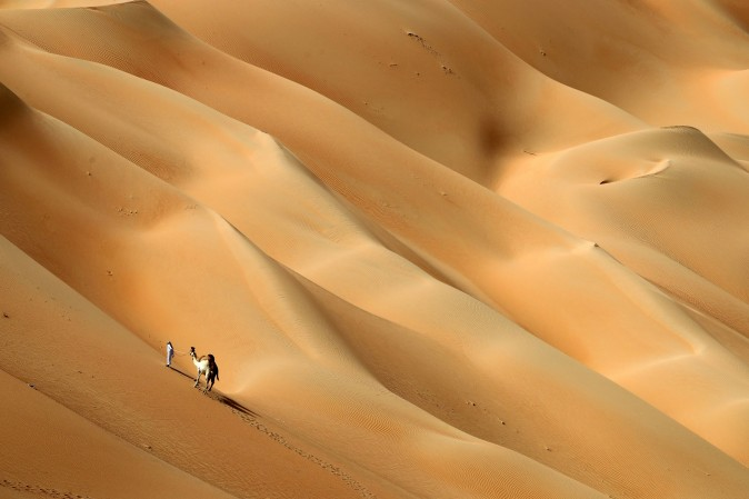 An Emirati man walks with his camels across the Hameem desert, some 170 kilometres west of the Gulf Emirate of Abu Dhabi, on Feb. 24. (KARIM SAHIB/AFP/Getty Images)
