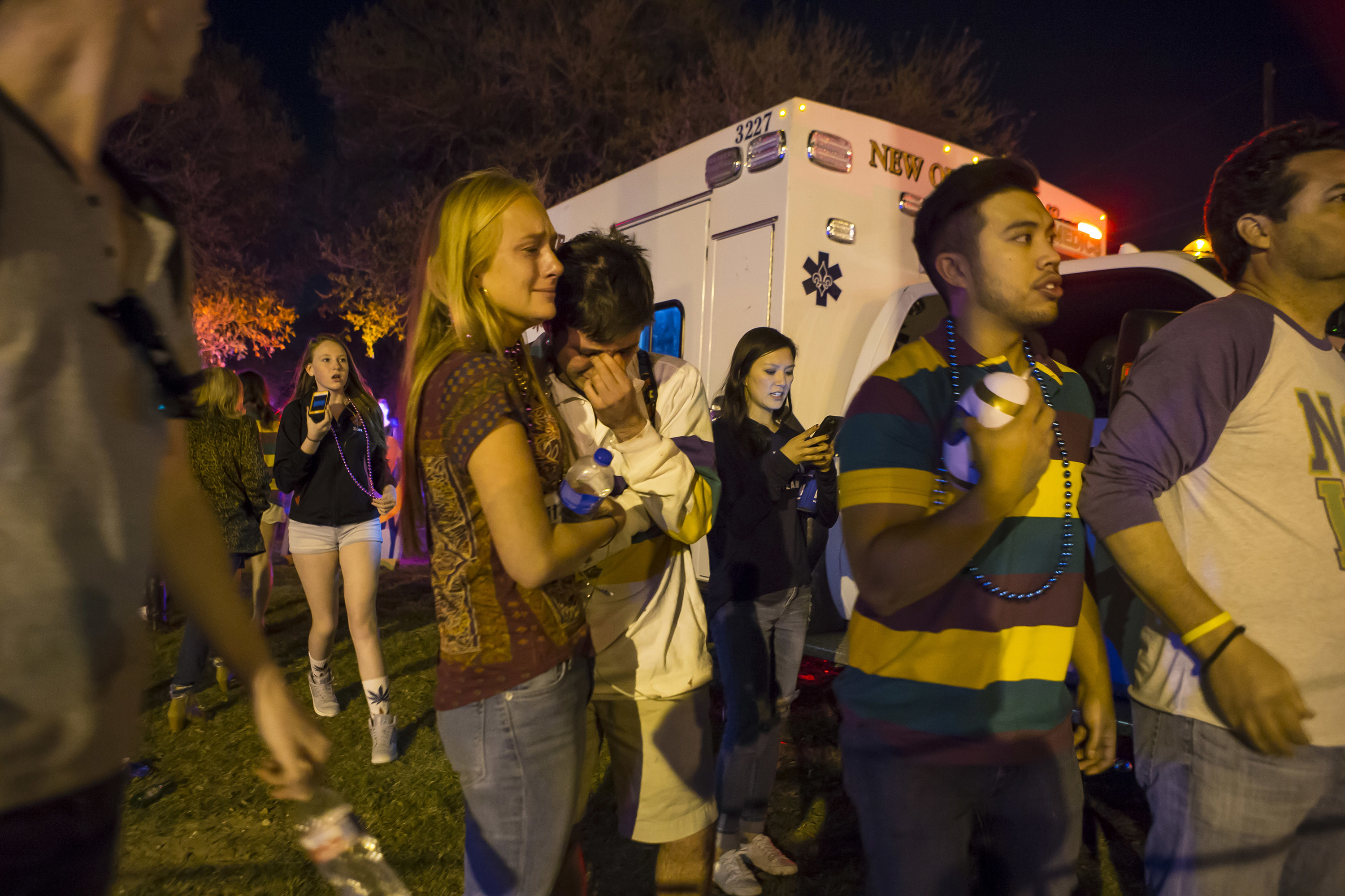 People hug and console each other as they watch New Orleans police work the scene where a vehicle plowed into a crowd injuring multiple people as the Krewe of Endymion parade rolled through New Orleans on Feb. 25, 2017. (Chris Granger/NOLA.com The Times-Picayune via AP)