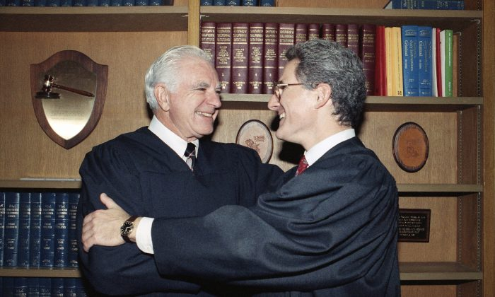 In this Friday, Oct. 13, 1989, file photo, retired Judge Joseph A. Wapner of TV's 'The People's Court' congratulates his son, Judge Frederick N. Wapner (R) as he was enrobed as a Municipal Court judge in Los Angeles. (AP Photo/Nick Ut, File)
