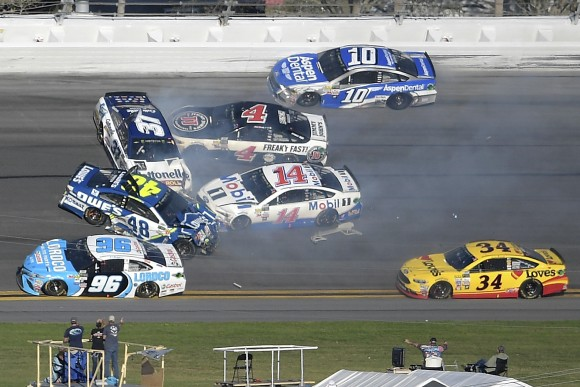 Jimmie Johnson (48), Clint Bowyer (14), Chris Buescher (37), Kevin Harvick (4), D.J. Kennington (96) and Danica Patrick (10) collide in a multi-car wreck between Turns 3 and 4, as Landon Cassill (34) drives past, during the NASCAR Daytona 500 auto race at Daytona International Speedway on Feb. 26, 2017, in Daytona Beach, Fla. (AP Photo/Phelan M. Ebenhack)
