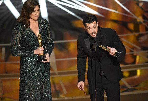 """Ezra Edelman, right, and Caroline Waterlow accept the award for best documentary feature for """"O.J.: Made in America"""" at the Oscars, Feb. 26, 2017, at the Dolby Theatre in Los Angeles. (Chris Pizzello/Invision/AP)"""