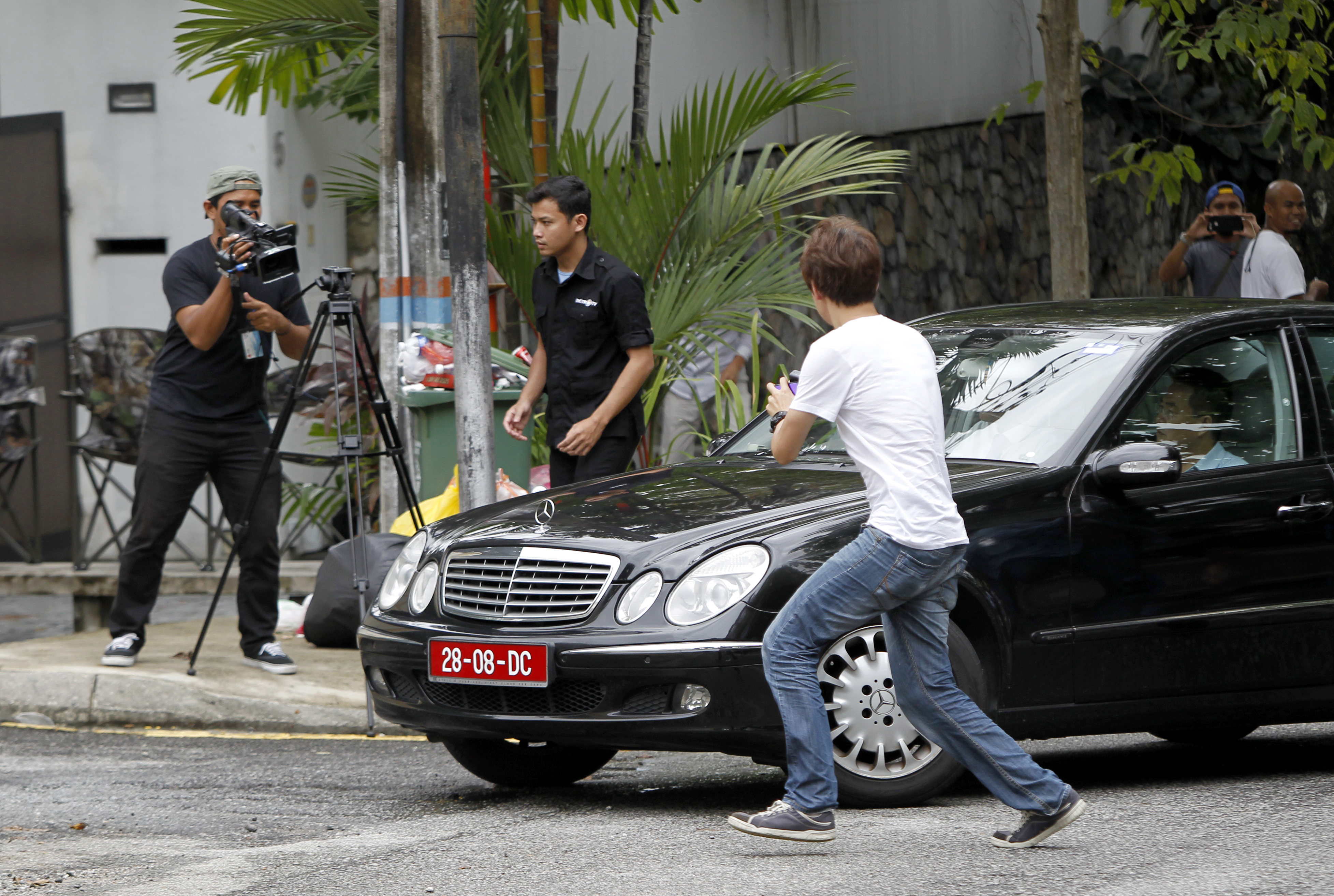 Journalists chase a car leaving North Korean Embassy in Kuala Lumpur, Malaysia on Feb. 27, 2017. (AP Photo/Daniel Chan)