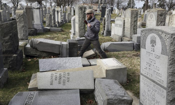 Rabbi Joshua Bolton of the University of Pennsylvania's Hillel center surveys damaged headstones at Mount Carmel Cemetery on in Philadelphia on Feb. 27, 2017. (AP Photo/Jacqueline Larma)