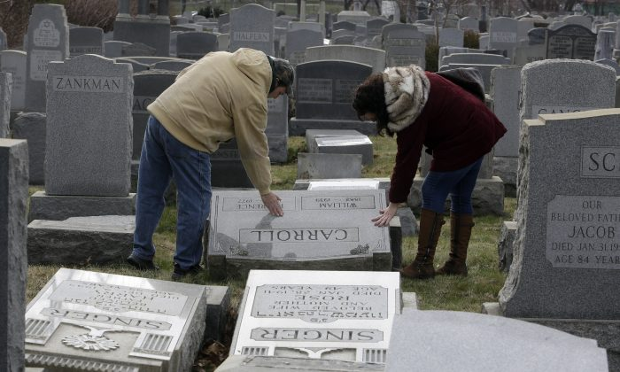 Joe Nicoletti and Ronni Newton of the Taconey Holmesburg town watch group pay their respects at a damaged headstone in Mount Carmel cemetery n Philadelphia on Feb. 27, 2017. (AP Photo/Jacqueline Larma)