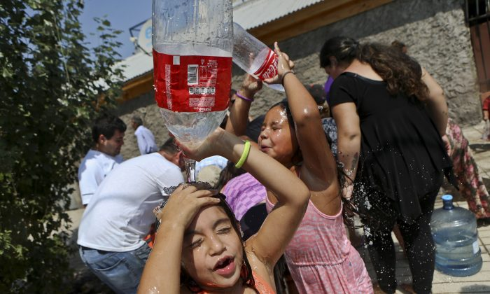 Two girls refresh themselves while residents gather water from a fire hydrant at a neighborhood in Santiago, Chile on Feb. 27, 2017. (AP Photo/ Esteban Felix)