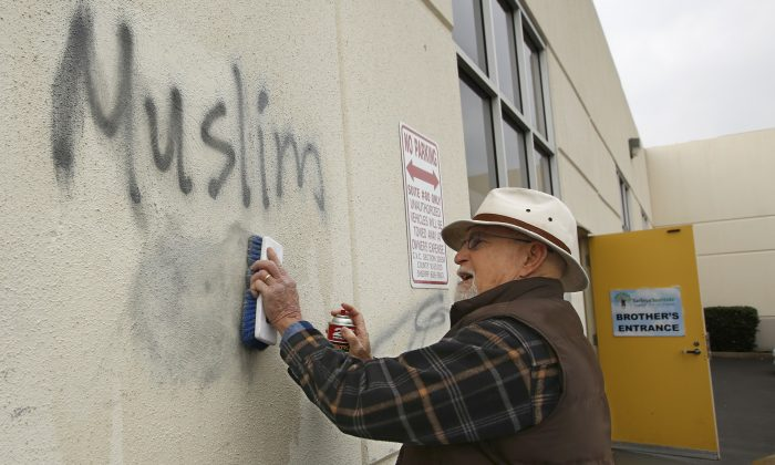 Tom Garing cleans up racist graffiti painted on the side of a mosque in what officials are calling an apparent hate crime in Roseville, Calif., on Feb. 1, 2017. (AP Photo/Rich Pedroncelli)