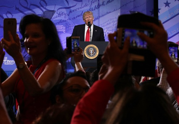 Attendees take pictures as President Donald Trump addresses the Conservative Political Action Conference at the Gaylord National Resort and Convention Center in National Harbor, Maryland on Feb. 24, 2017. (Alex Wong/Getty Images)