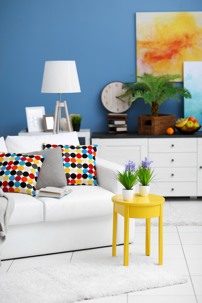 A rich blue feature wall makes a striking backdrop for a soft white sofa and a mix of colourful accessories. (Africa studio/Shutterstock)