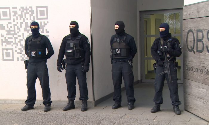 Police stand in front of a residential building in Berlin, Germany on Feb. 28, 2017 after a raid in connection with the ban of the Fussilet 33 organization.  (TeleNewsNetwork/dpa via AP)