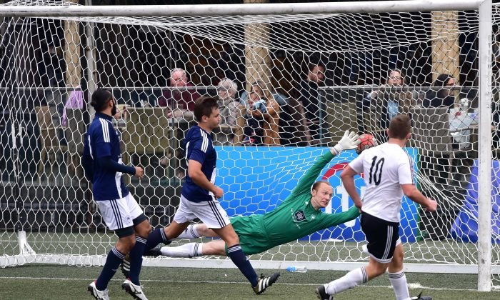Adam Wise of GAS equalizes past Wanderers' Freddy Toomer late in normal time to take the game into 2 10-minute periods of Extra Time in the Yau Yee League Cup Quarter Final match at Sports Road on Sunday Feb 26. Wanders went on to win a close match 2-1. (Bill Cox/Epoch Times)