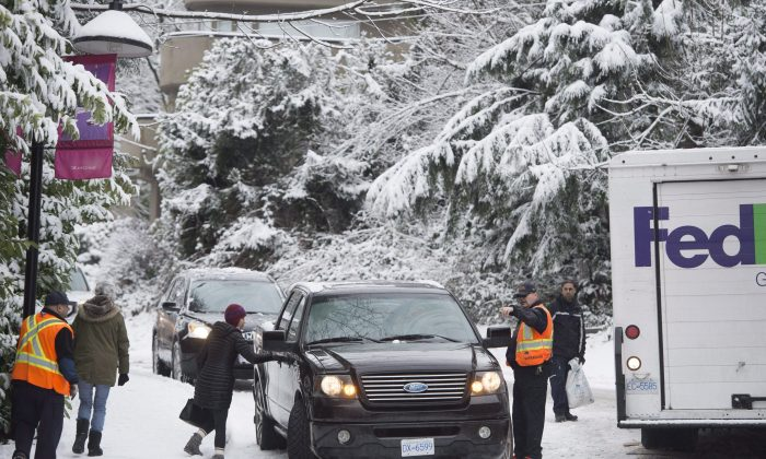 =Vehicles get stuck on a snow-covered side street in North Vancouver on Feb. 3, 2017. The Weather Network spring forecast calls for Canadians to expect more storms before the wintry weather ends. (The Canadian Press/Jonathan Hayward)