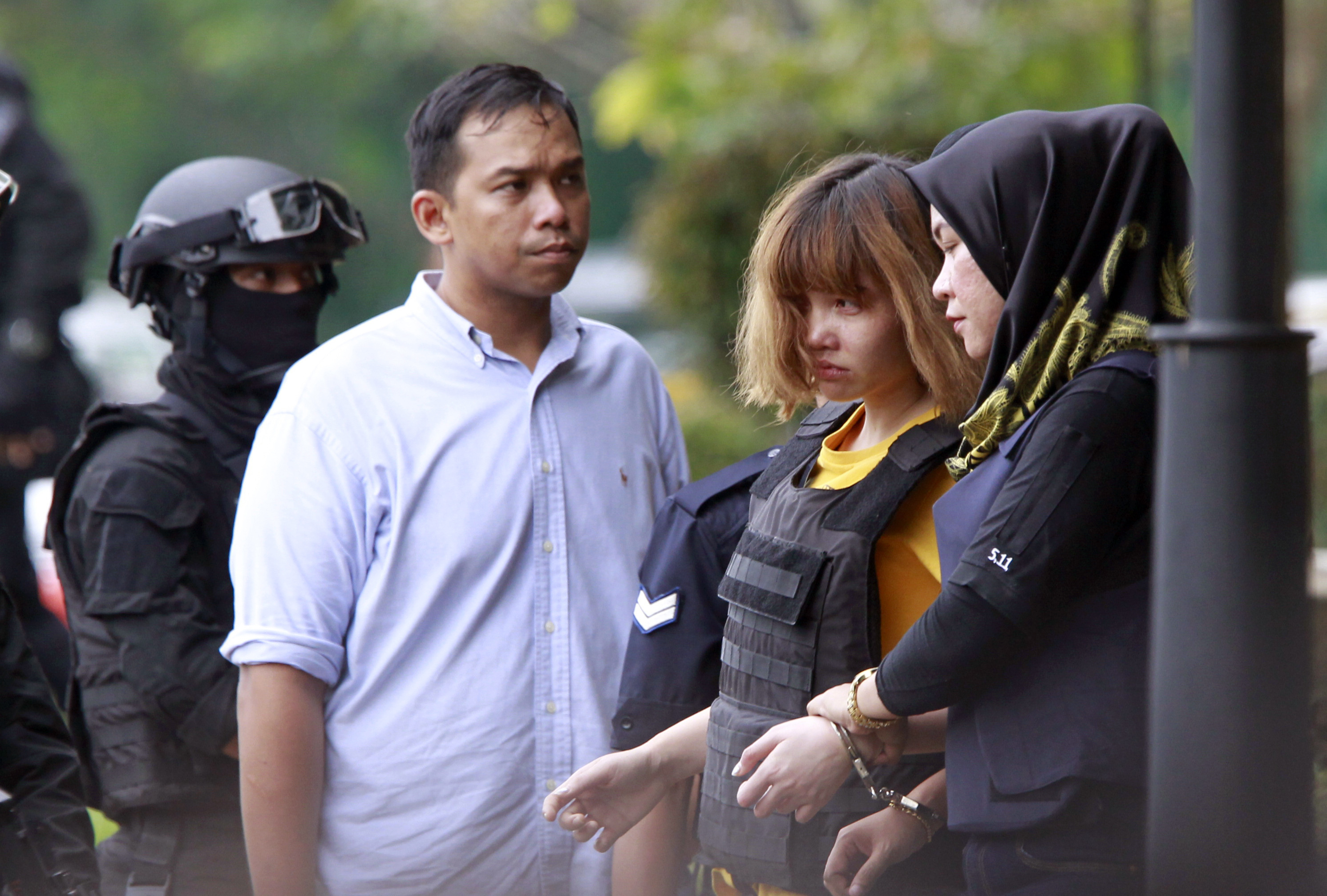 Vietnamese suspect Doan Thi Huong, second from right, in the ongoing assassination investigation, is escorted by police officers out from Sepang court in Sepang, Malaysia on March 1, 2017. (AP Photo/Daniel Chan)