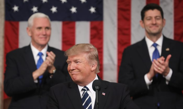 Vice President Mike Pence (L) and Speaker of the House Paul Ryan (R) applaud as U.S. President Donald J. Trump (C) delivers his first address to a joint session of the U.S. Congress in the House chamber of the U.S. Capitol in Washington on Feb. 28, 2017. Trump's first address to Congress focused on national security, tax and regulatory reform, the economy, and healthcare. (Jim Lo Scalzo - Pool/Getty Images)