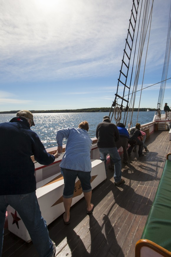 Passengers help hoist a sail on the Victory Chimes ship off the coast of Maine on Sept. 28, 2016. (Channaly Philipp/Epoch Times)