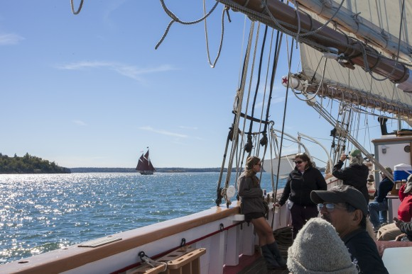 Passengers aboard the Victory Chimes while away the afternoon, as the The Angelique windjammer sails in the distance. (Channaly Philipp/Epoch Times)