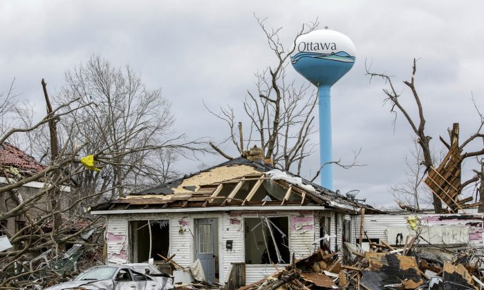 Debbie Loughridge's damaged home and car are seen among debris in Naplate, Ill., on March 1, 2017. (AP Photo/Teresa Crawford)