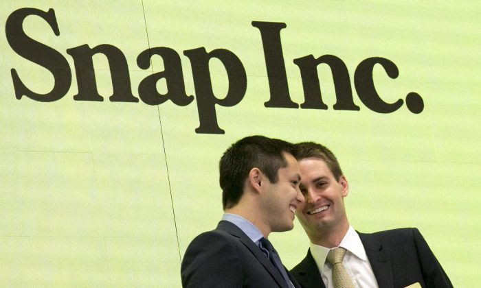 Snapchat co-founders Bobby Murphy (L) and CEO Evan Spiegel ring the opening bell at the New York Stock Exchange as the company celebrates its IPO on March 2, 2017. (AP Photo/Richard Drew)