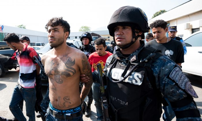 Honduran police commandos arrest members of the Mara Salvatrucha (MS-13) gang in San Pedro Sula, 180 km north of Tegucigalpa, on Feb. 17, 2017. The MS-13 gang is allegedly connected to the cases of extortion against the public transport that have left 12 people killed so far this year and 215 in 2016. (JORDAN PERDOMO/AFP/Getty Images)