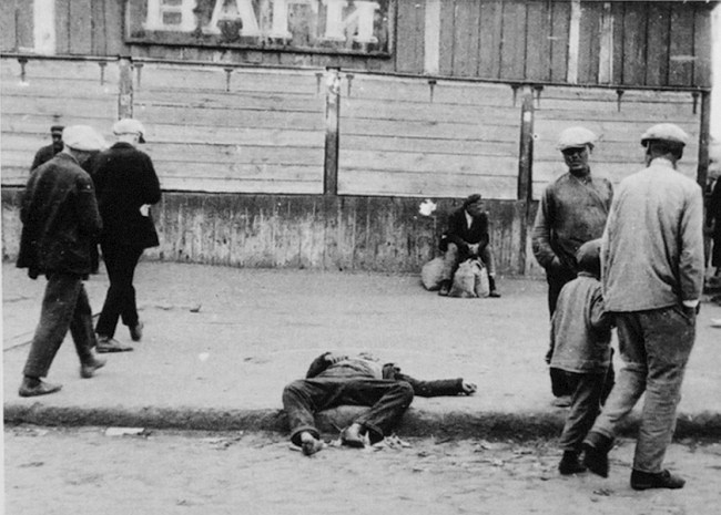 Passers-by and the corpse of a starved man on a street in Kharkiv, 1932 (Public Domain)