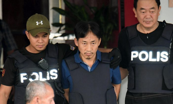 North Korean Ri Jong Chol, center, who was arrested in connection with the death of Kim Jong Un's half-brother, is transferred from Sepang district police station in Sepang, Malaysia on March 3, 2017. (Muneyoshi Someya/Kyodo News via AP)